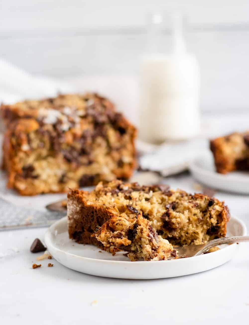 Slice of coconut chocolate chip banana bread on white plate with loaf cooling behind it.
