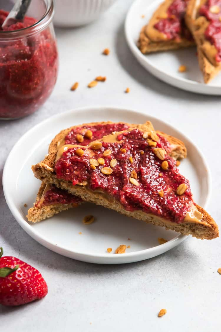 Strawberry chia jam on peanut butter toast slices on white plate.