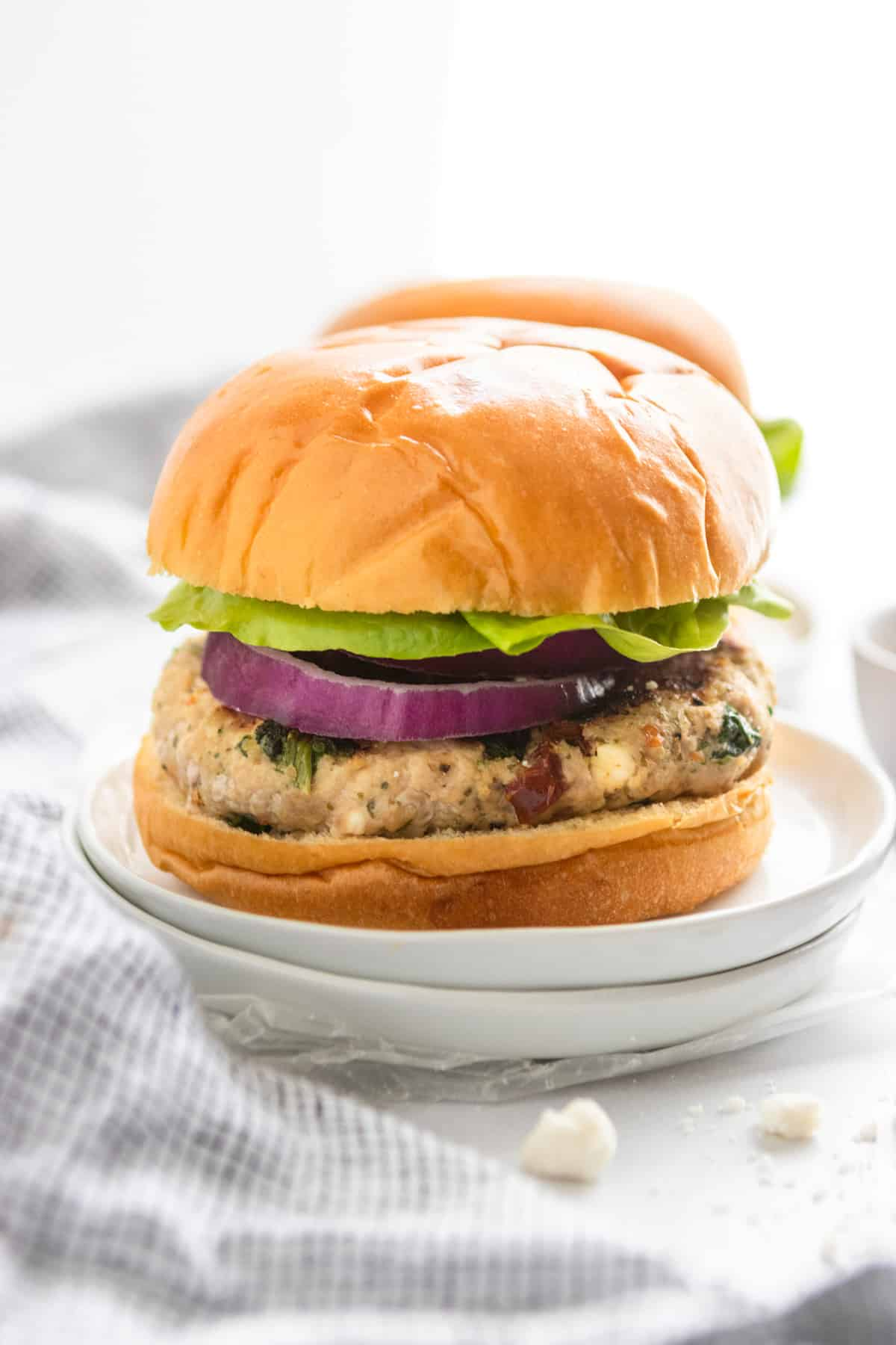 Sun-dried tomato feta turkey burger on bun with lettuce and onion.