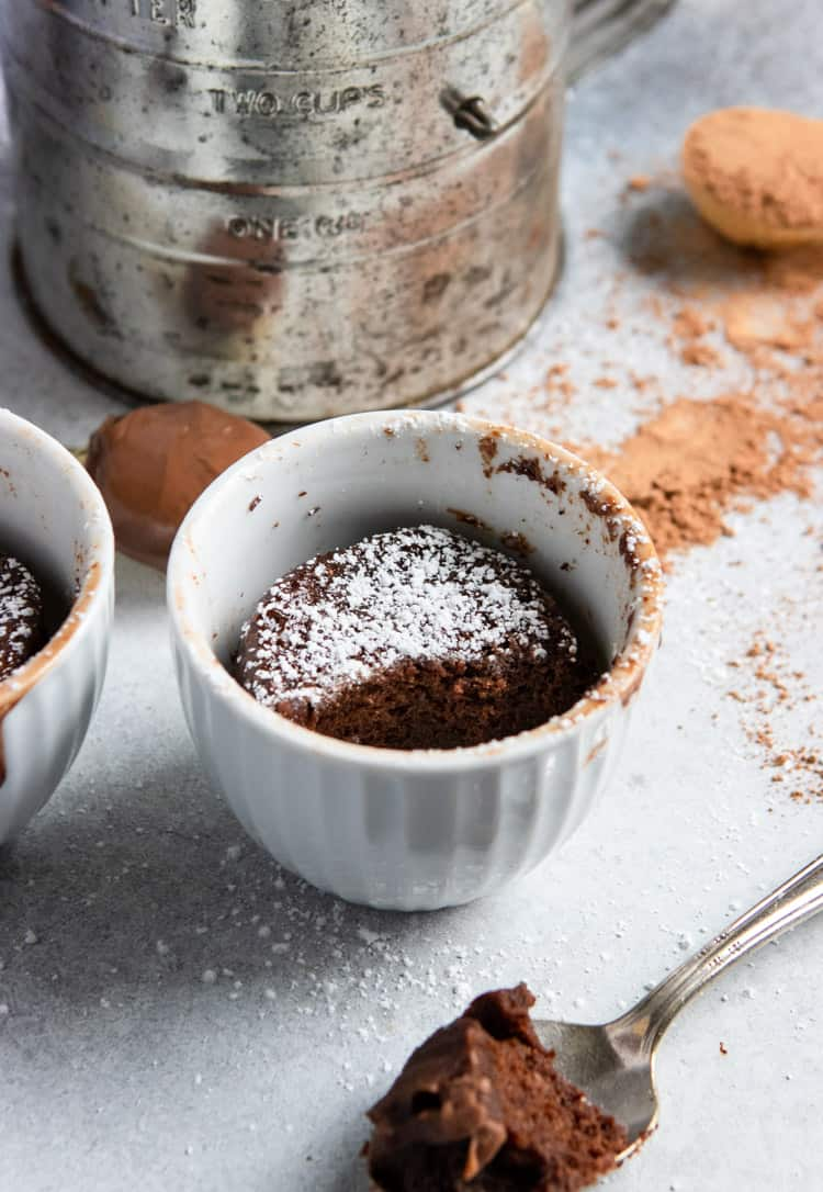 Nutella chocolate mug cake in a white dish with powdered sugar