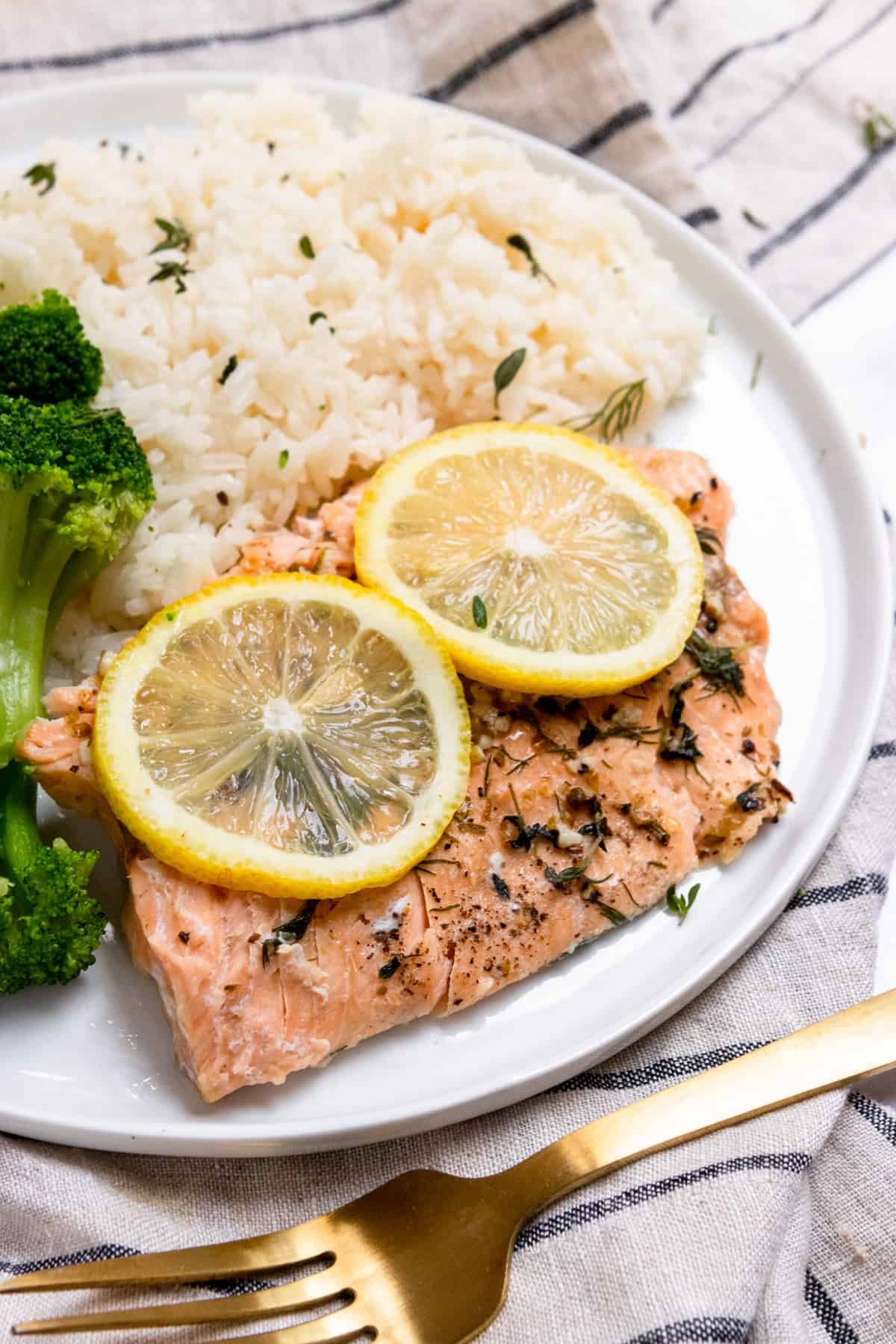 Salmon with lemon and herbs on plate with rice.