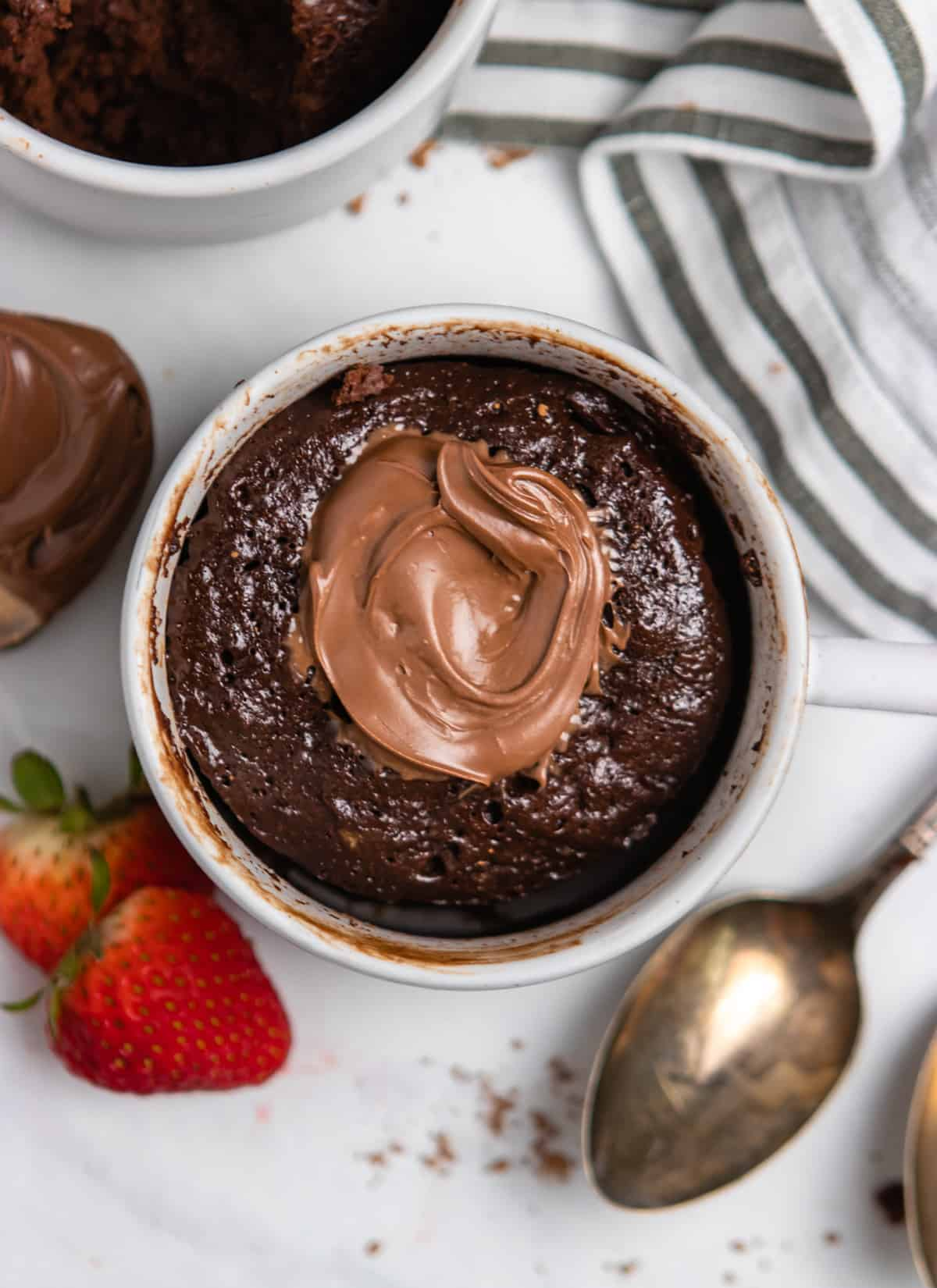 Overhead view of nutella chocolate cake in mug with strawberries and spoon.