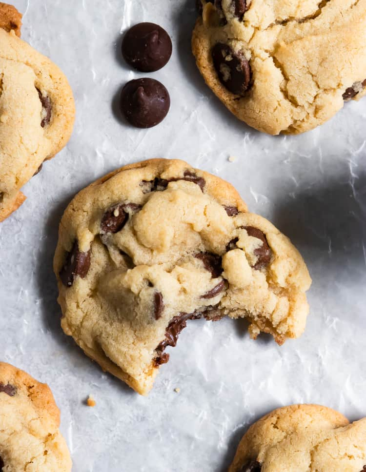 Overhead of small batch chocolate chip cookies with bite out of one cookie.