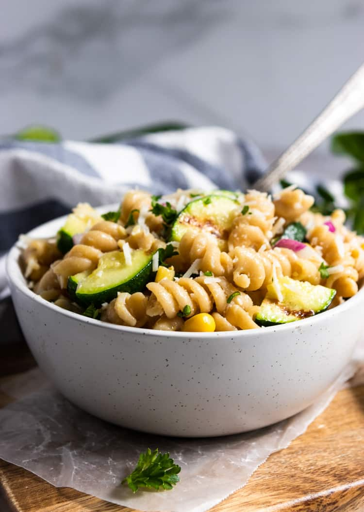 Bowl of pasta salad with serving spoon.