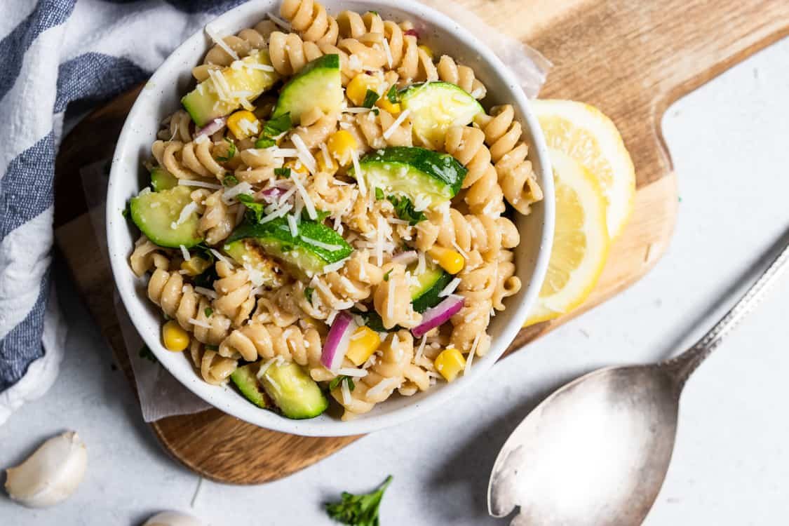 White bowl of pasta salad with lemon wedges and spoon.