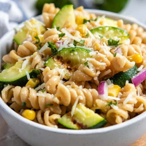 Zucchini pasta salad in bowl with fresh corn and shredded parmesan.