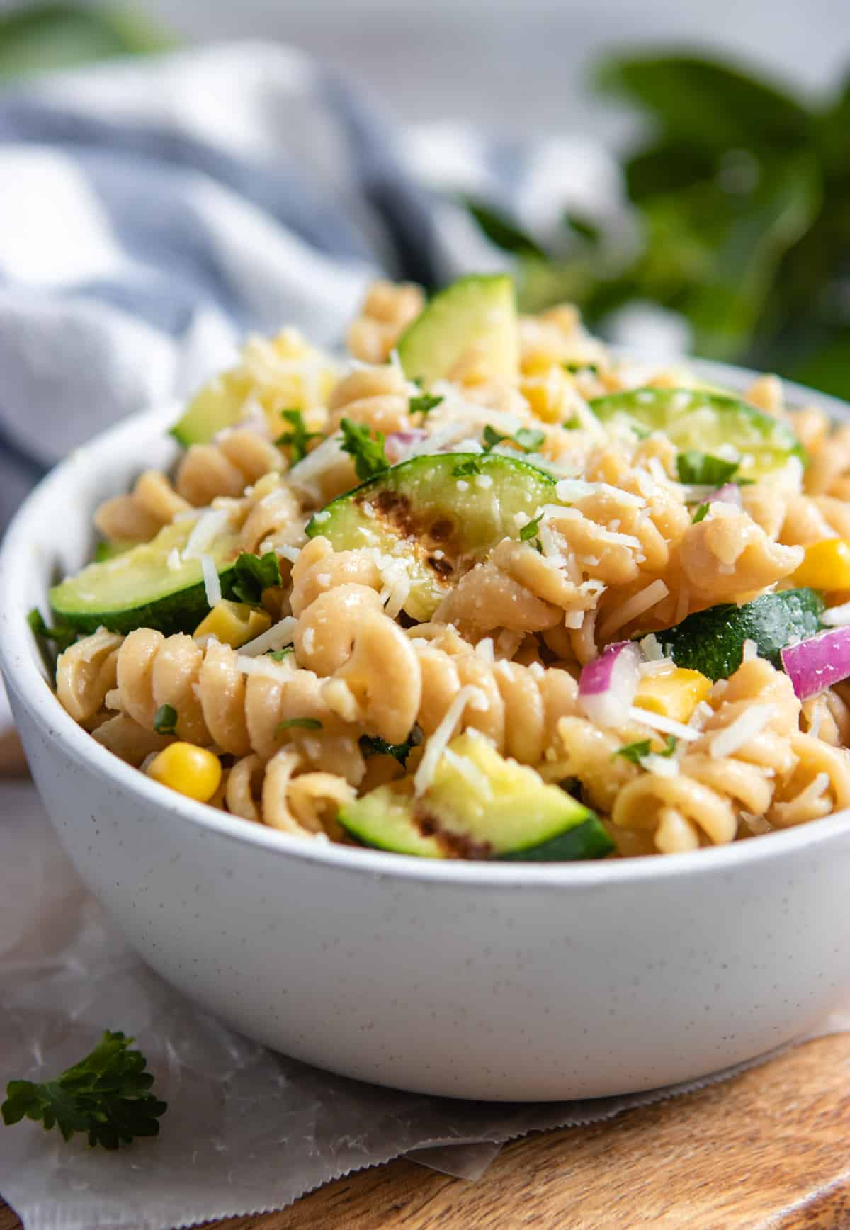 Bowl with pasta salad with grilled zucchini, red onion, corn and cheese.