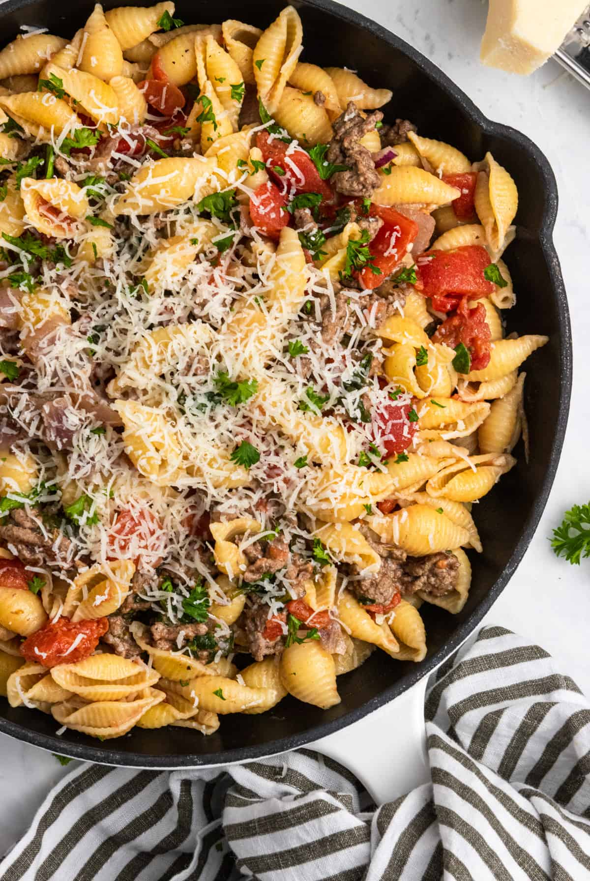 ground beef pasta in cast iron skillet with cheese.