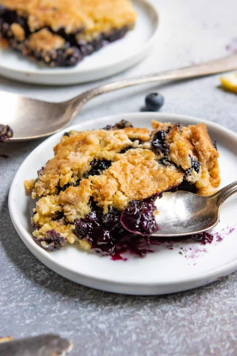 Blueberry dump cake with lemon on white plate with spoon.