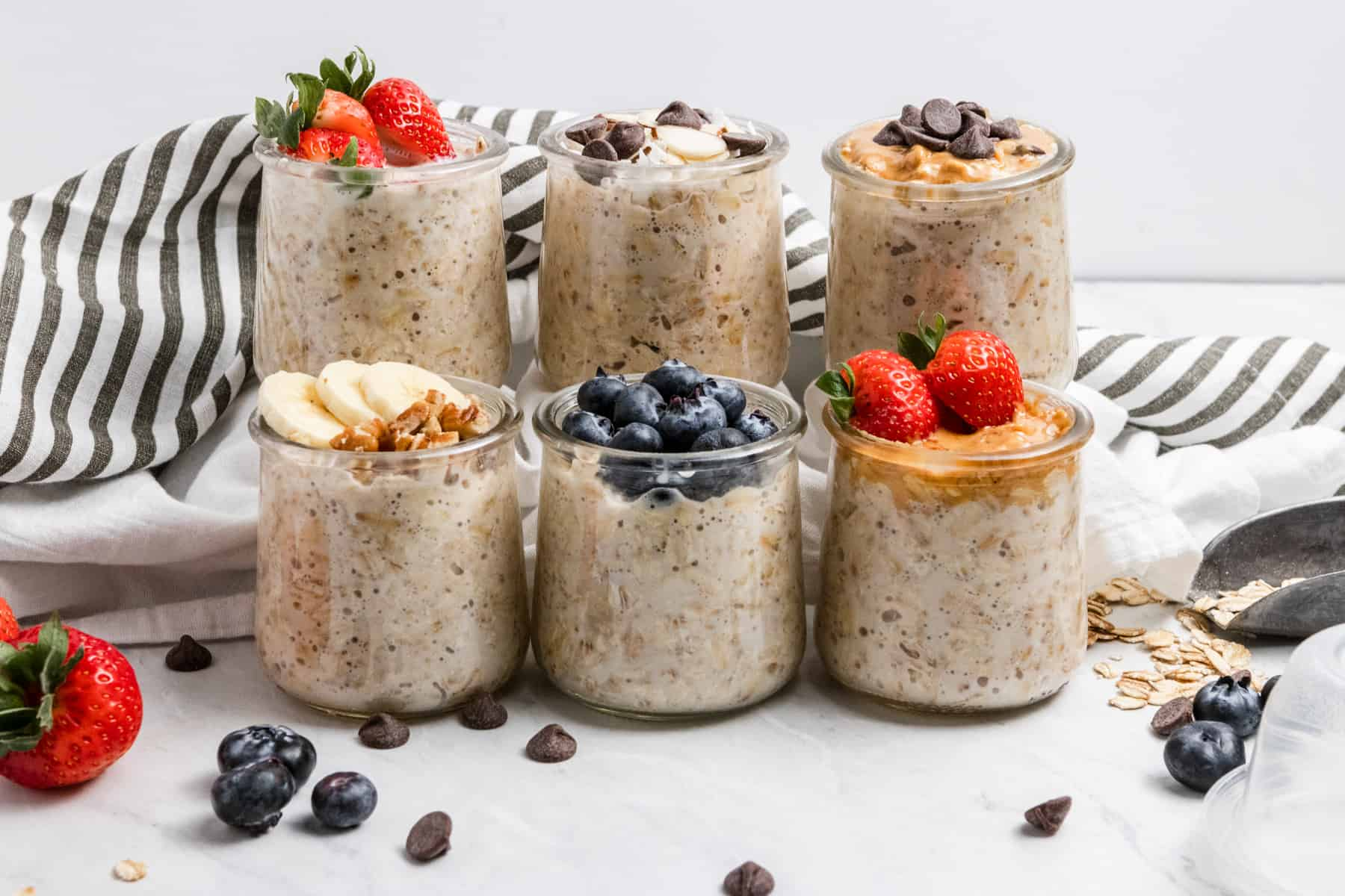 6 jars of overnight oats with ingredients surrounding.