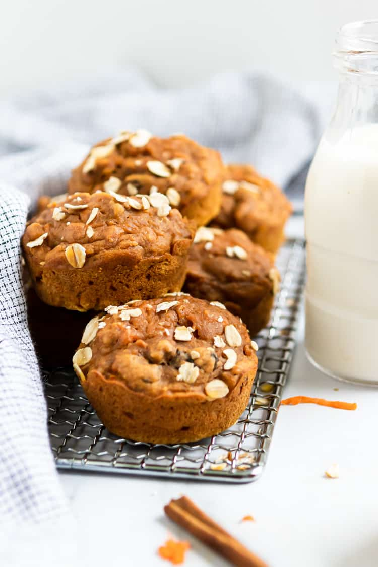 Muffins on rack with glass of milk.