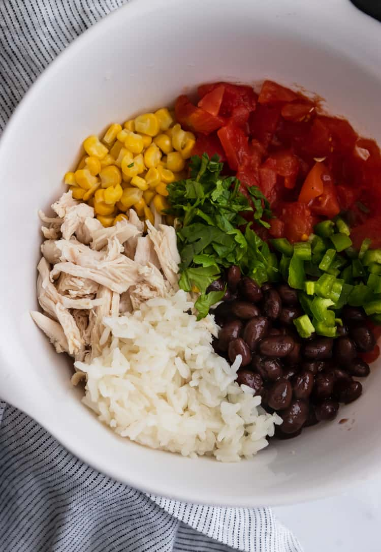 Bowl with recipe ingredients: rice, chicken, corn, cilantro, tomatoes and jalapeño.