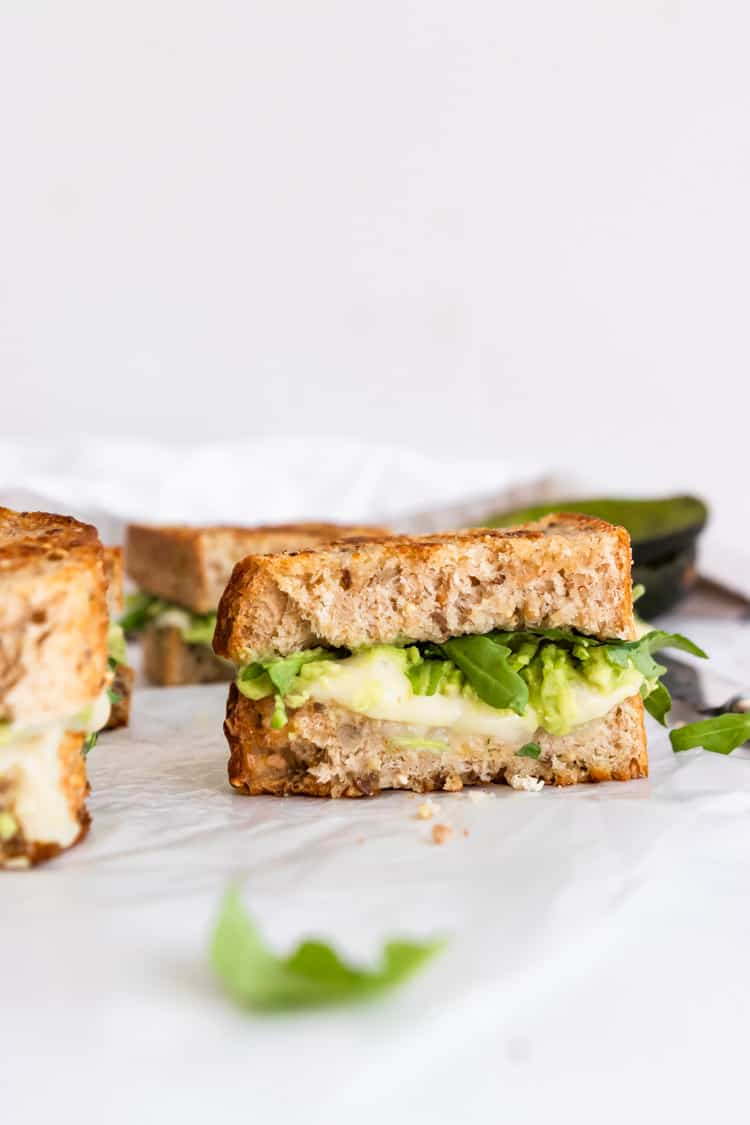 Half of a havarti grilled cheese with avocado and arugula.