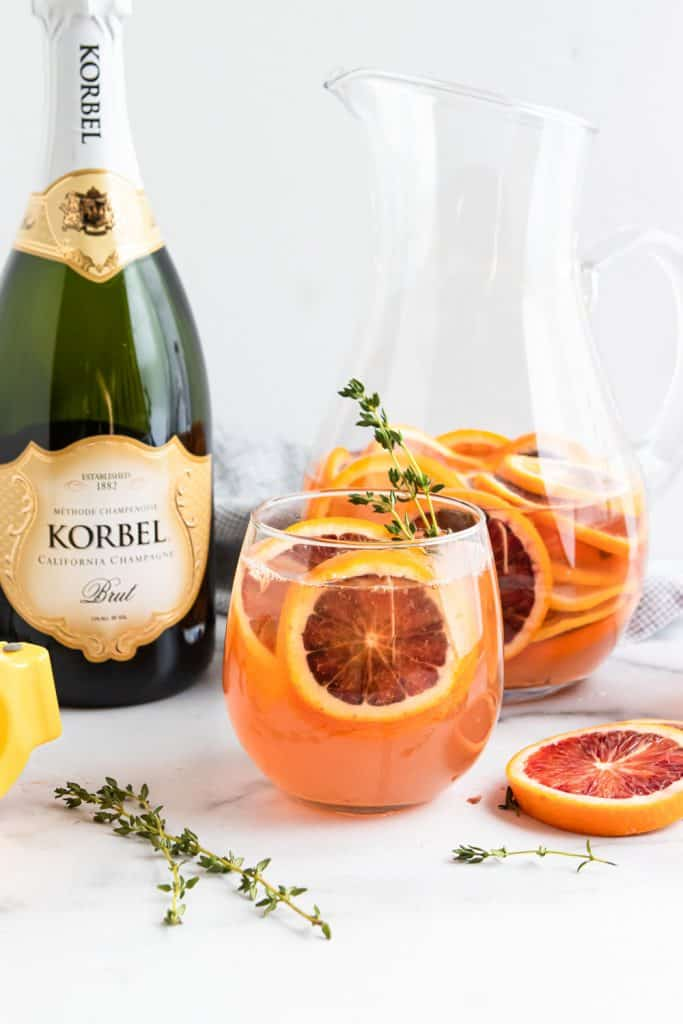 Glass and pitcher of Blood Orange Champagne Sangria with bottle of champagne.