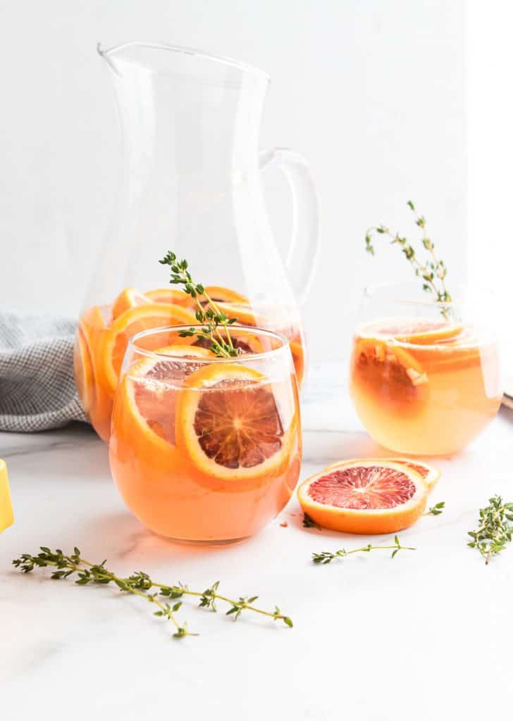 Glass and pitcher of Blood Orange Champagne Sangria.