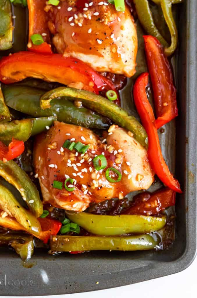Chicken and peppers on sheet pan with sesame seeds and green onion.