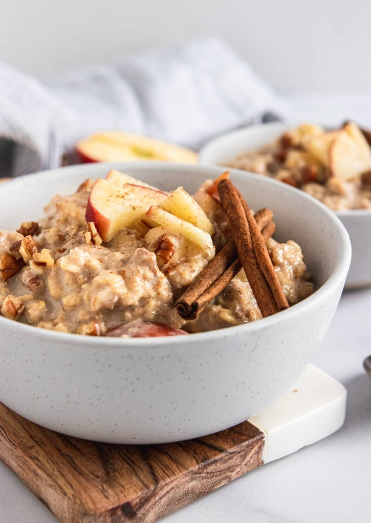 Apple oatmeal in bowl with apples and cinnamon sticks.