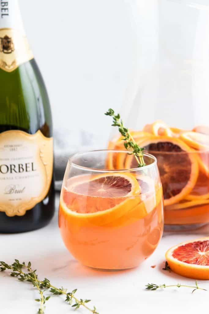 Blood Orange Champagne Sangria in glass with sprig of thyme.
