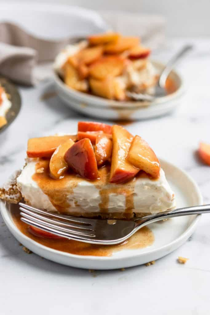 Slice of No Bake Caramel Apple Cheesecake with fork and caramel drizzle.