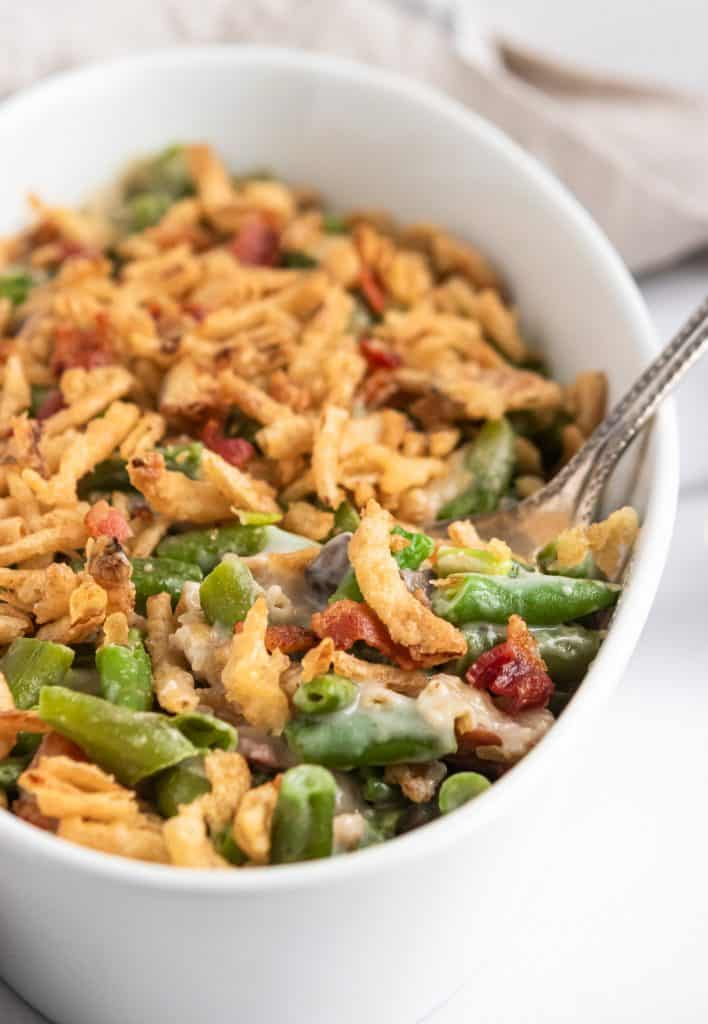 Parmesan Bacon Green Bean Casserole with serving spoon.