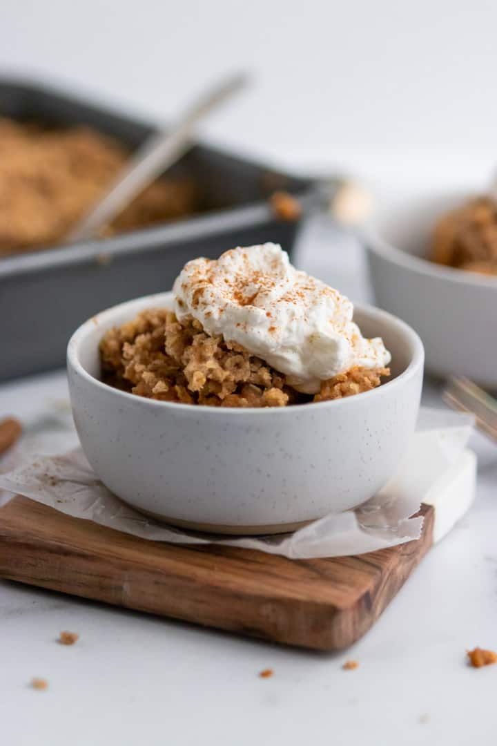 Pumpkin Pie Crumble served in bowl with whipped cream and cinnamon.