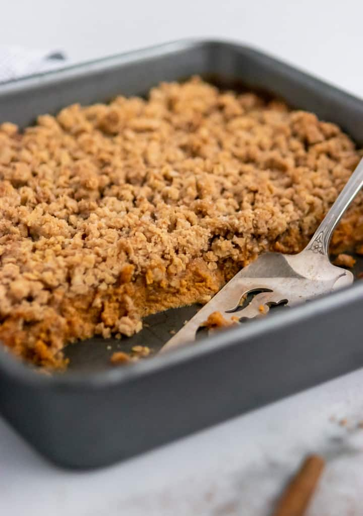 Pan of Pumpkin Pie Crumble with serving spoon.