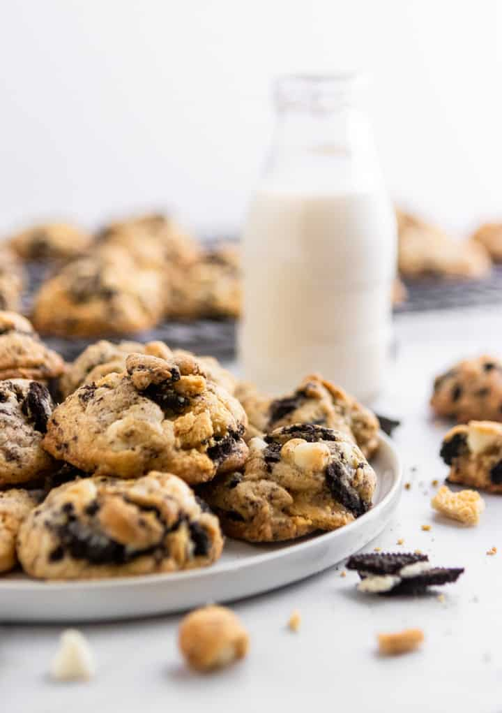 Loaded Cookies and Cream Cookies on plate with glass of milk.