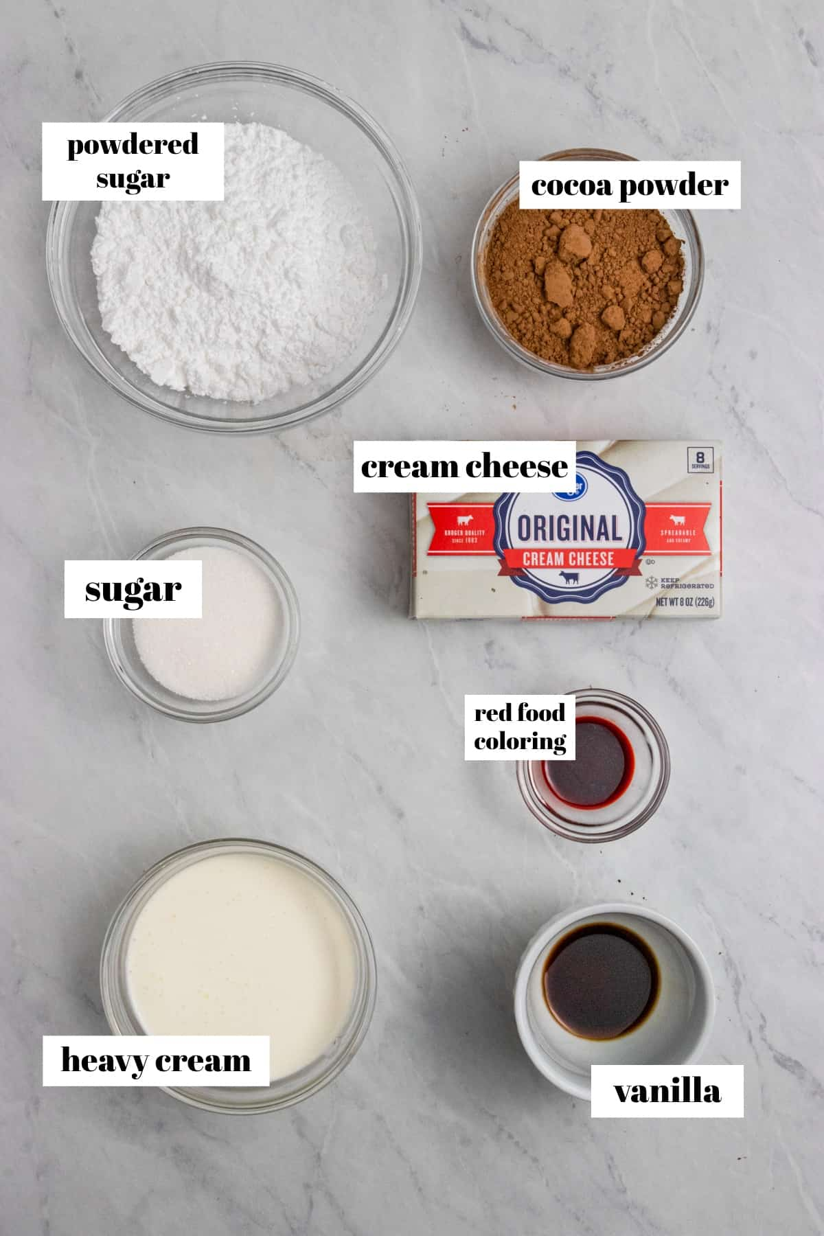 Cream cheese, powdered sugar, cocoa powder and other ingredients labeled on counter.