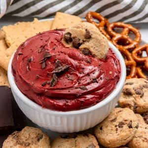Red velvet cheesecake dip in white bowl with chocolate chip cookie.