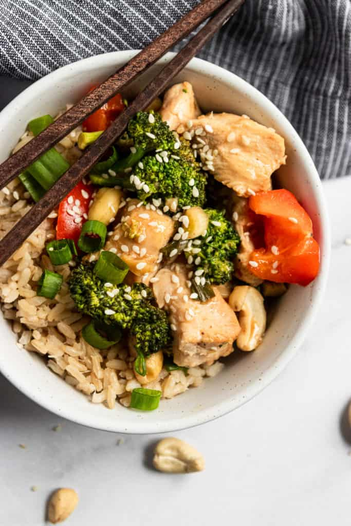 Overhead shot of rice bowl with Baked cashew chicken with sesame seeds and chopsticks.