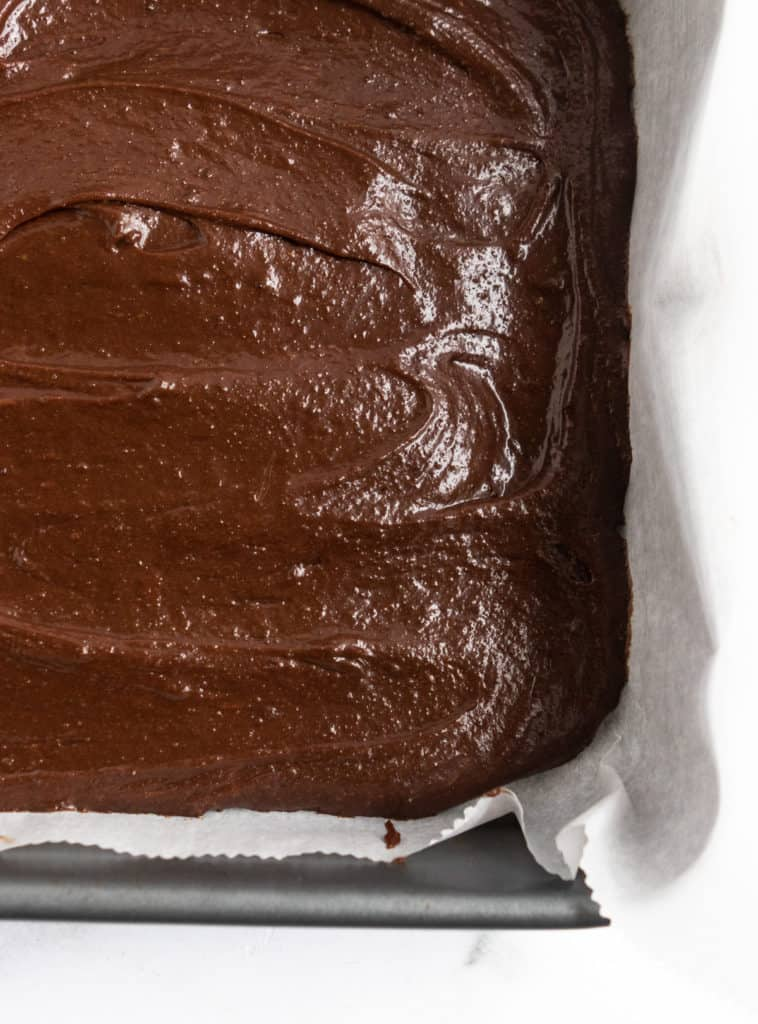 Brownie batter in parchment lined pan.