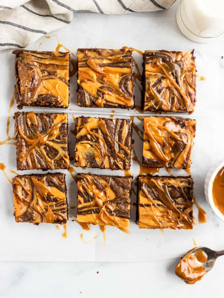 Overhead shot of sliced brownies with dulce de leche drizzle.