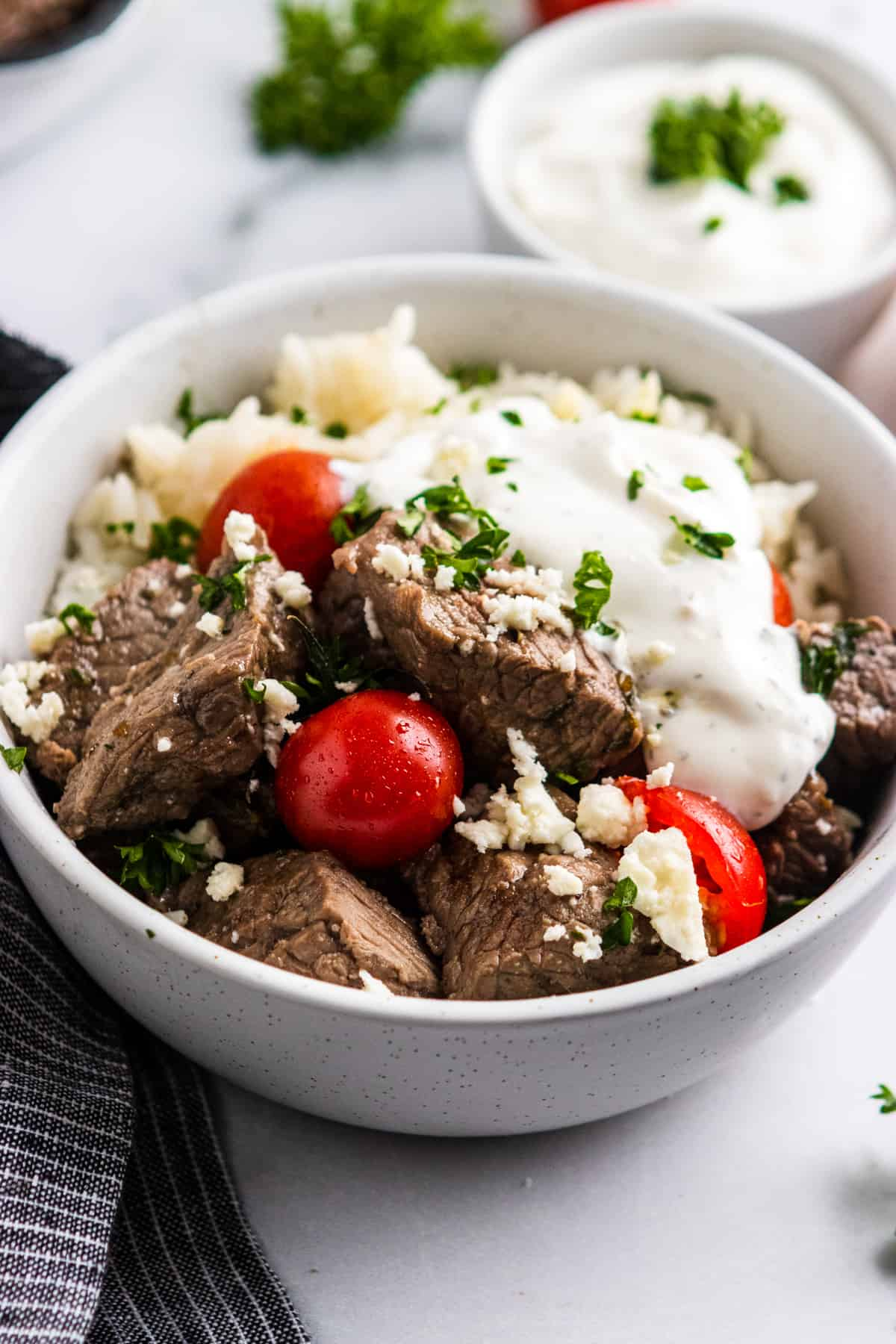 Rice bowl with steak, tomatoes, feta and yogurt dill sauce.