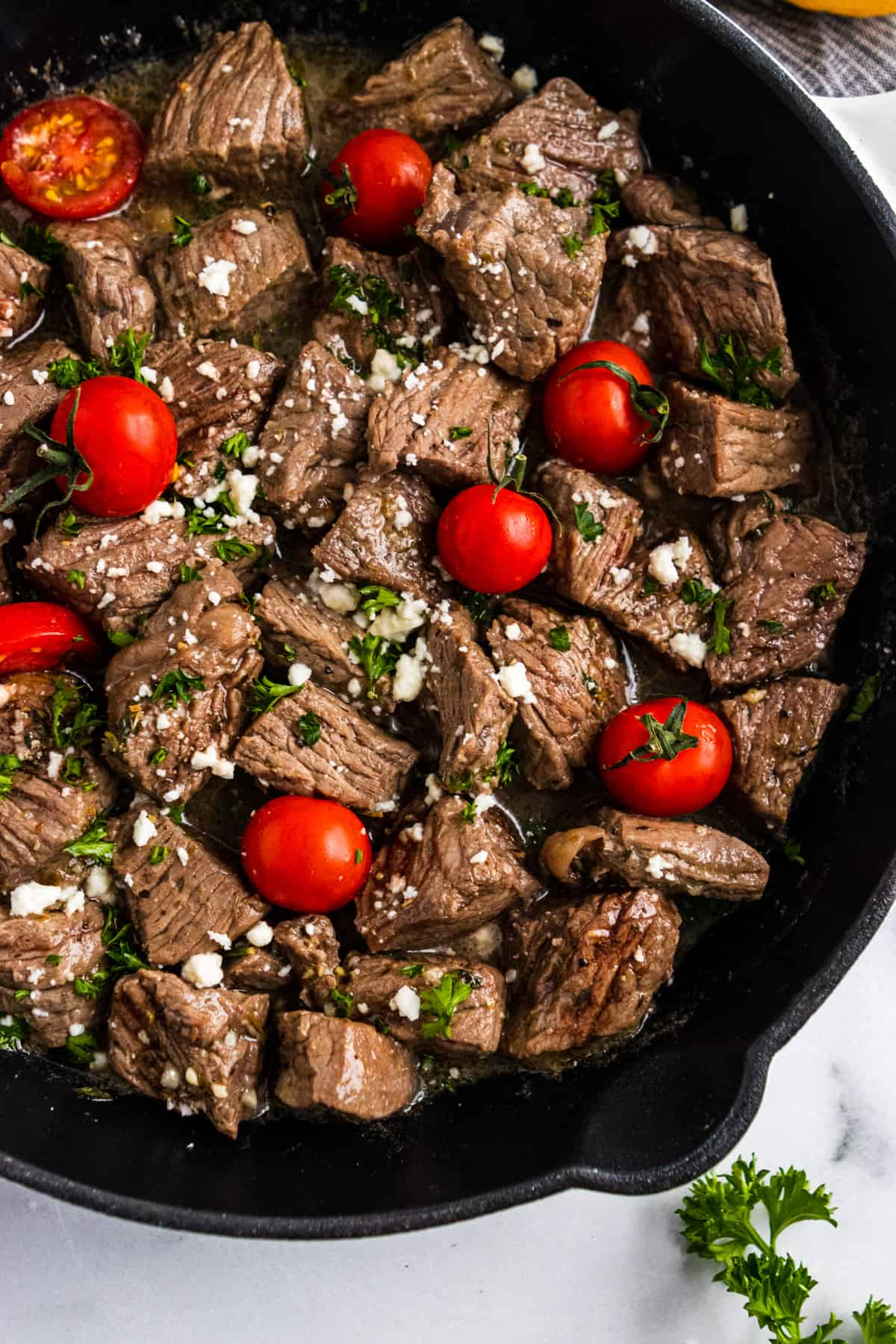 Steak bites in skillet with fresh tomatoes, feta and parsley.