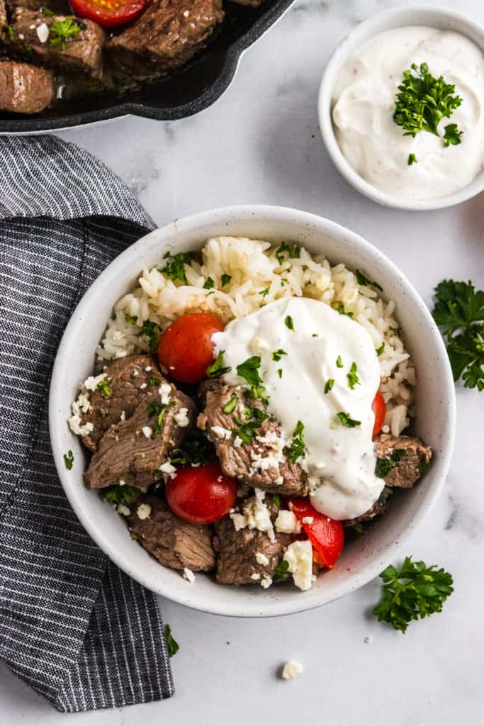 Overhead shot of bowl with steak bites, tomatoes, parsley, feta and yogurt sauce.