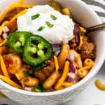 Chili mac and cheese in bowl with sour cream and jalapeno.