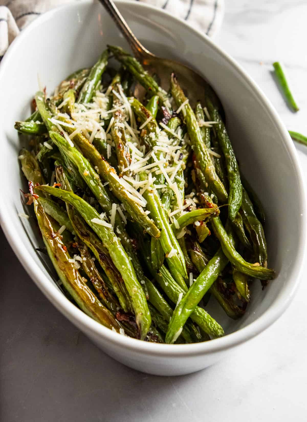 White serving bowl with roasted green beans.
