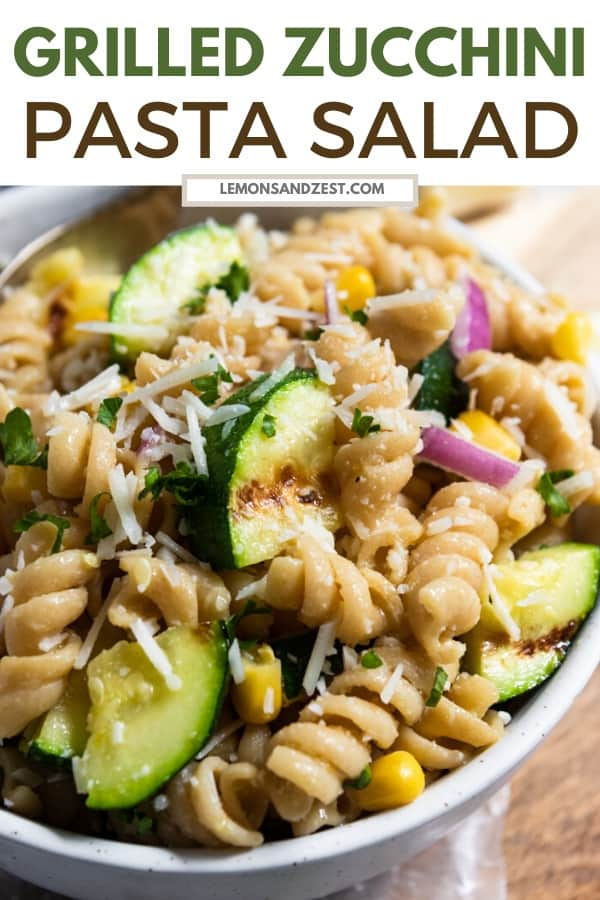 Pasta salad in bowl with zucchini and corn.