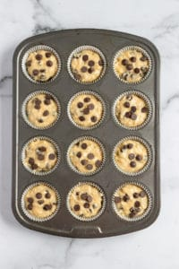 muffin batter in tin with chocolate chips on top.