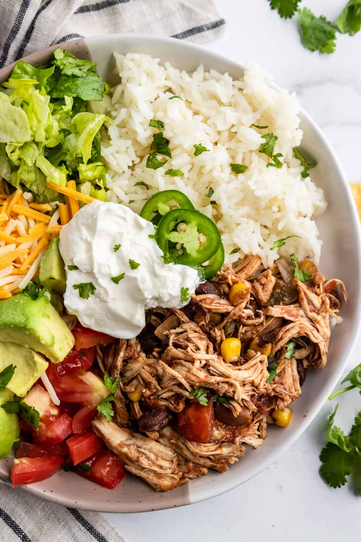 Chicken burrito bowl with lettuce, rice, avocado, tomato, cheese and sour cream.