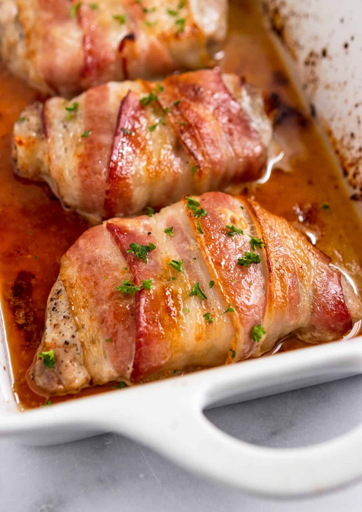 Bacon wrapped pork chops in white pan with parsley.