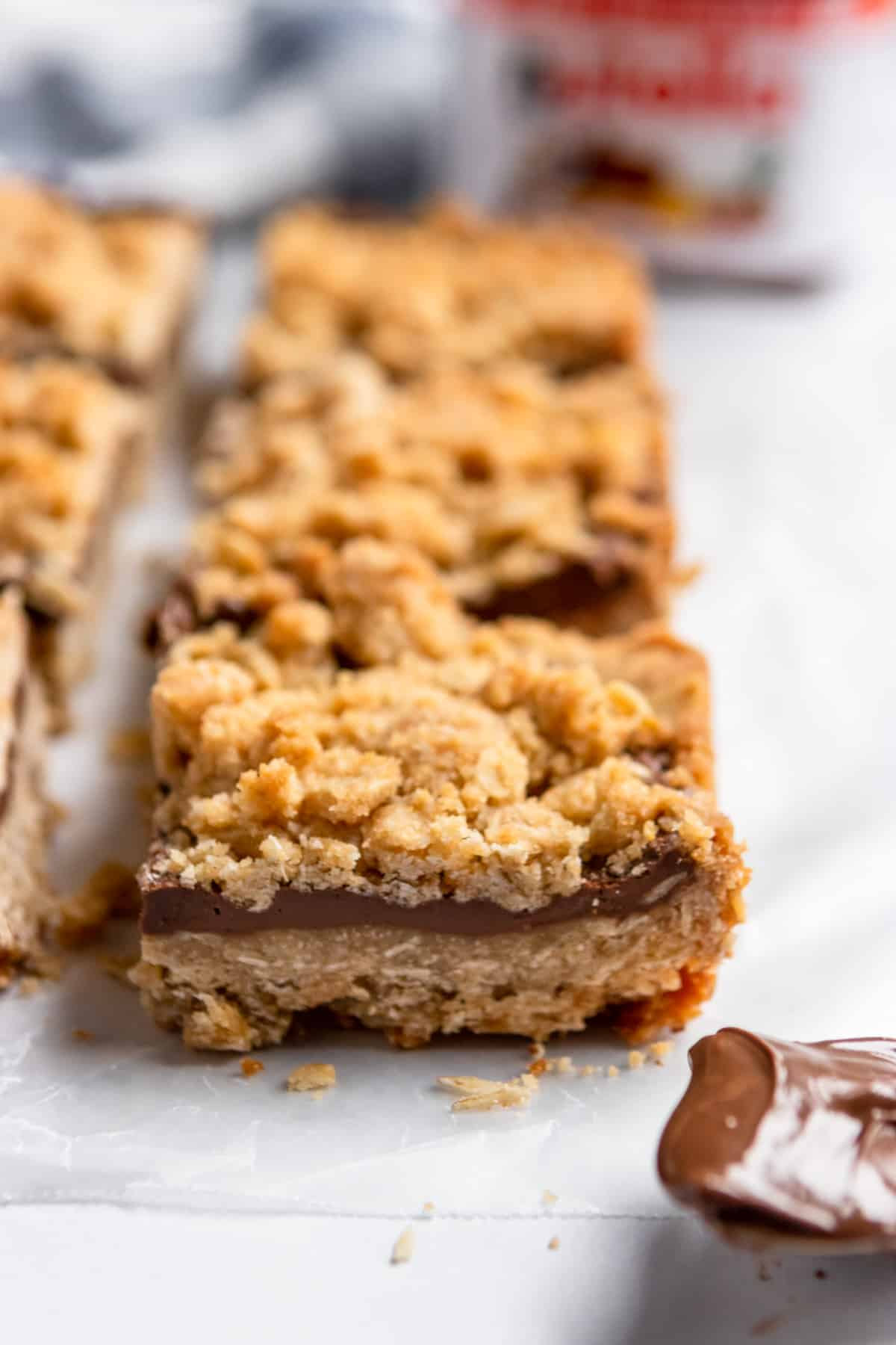 Oat crumble bar with spoon of Nutella.