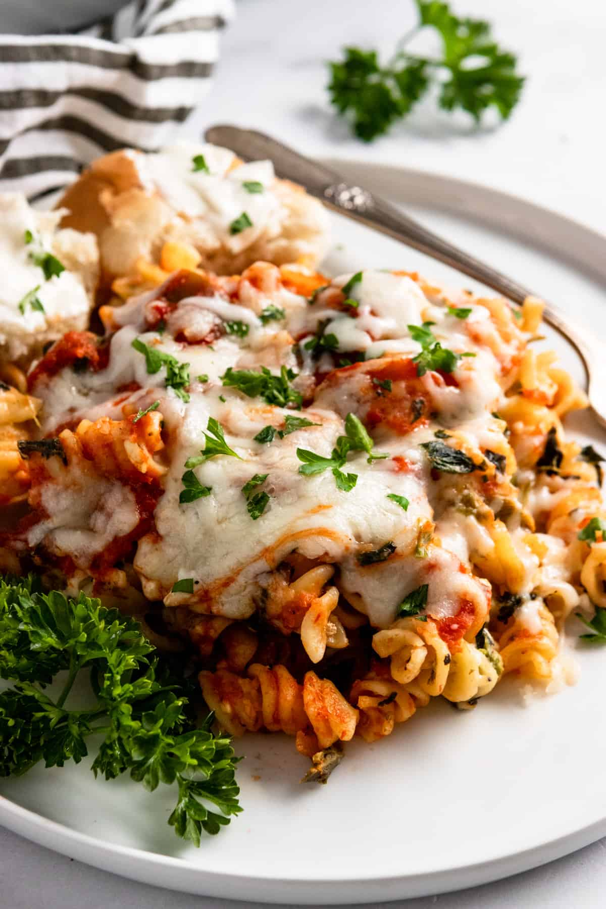Easy baked pasta on white plate with parsley.