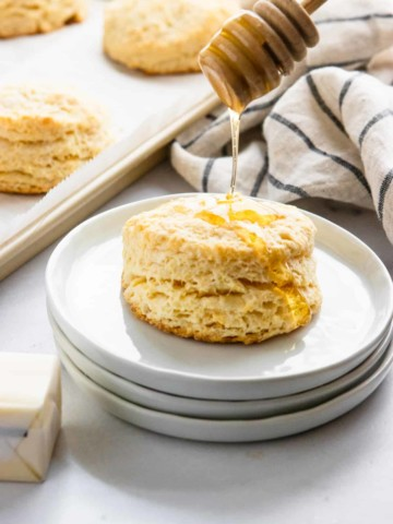 Biscuit on plate with honey drizzle.