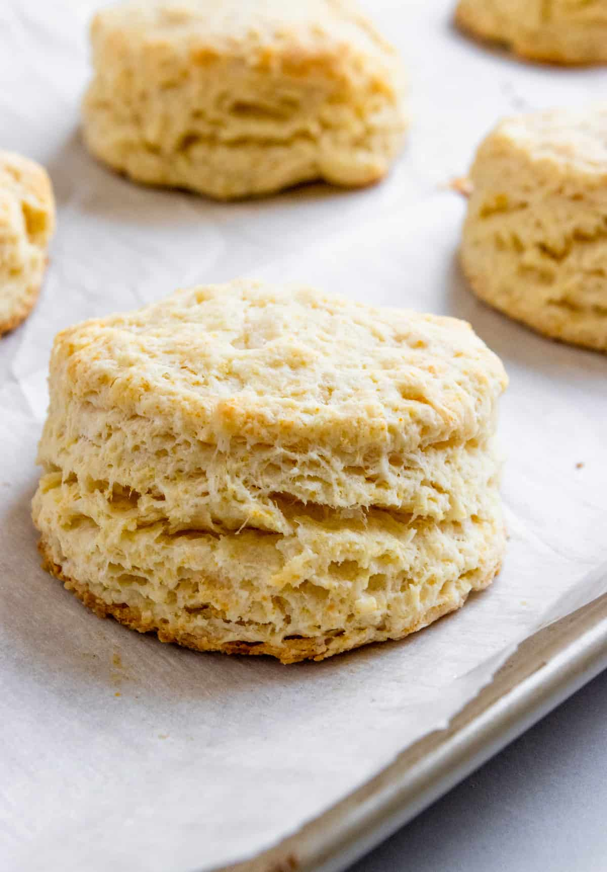 Flaky biscuits on baking sheet.