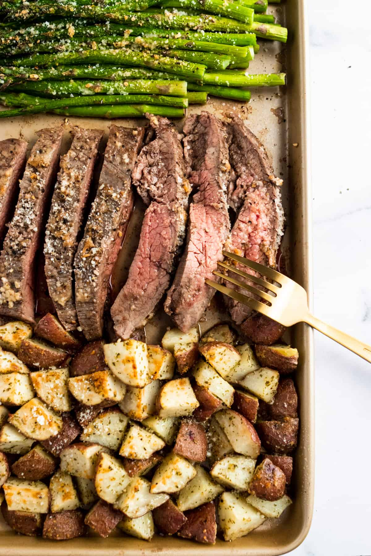 Parmesan crusted steak with potatoes and asparagus on sheet pan.