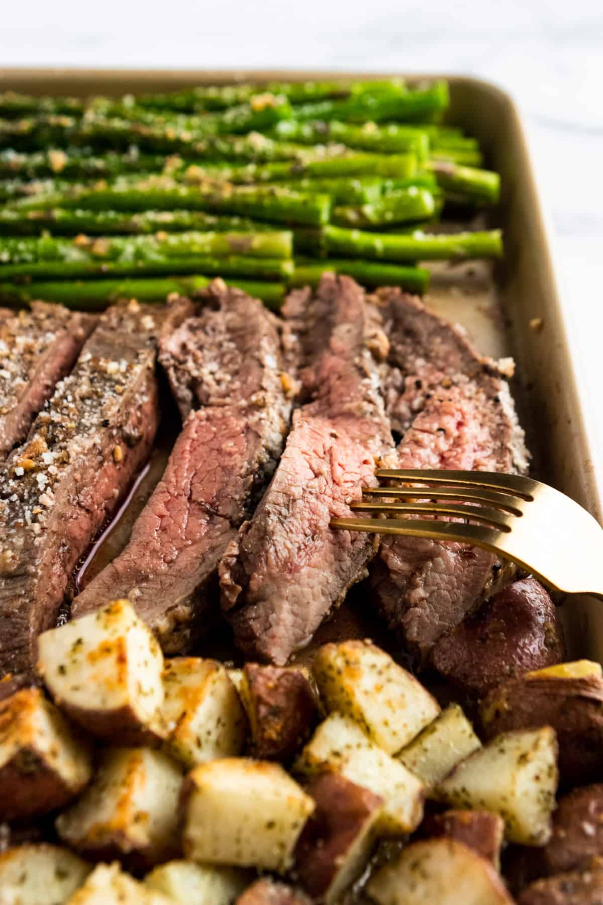 Parmesan crusted Flank steak sliced on sheet pan with fork.