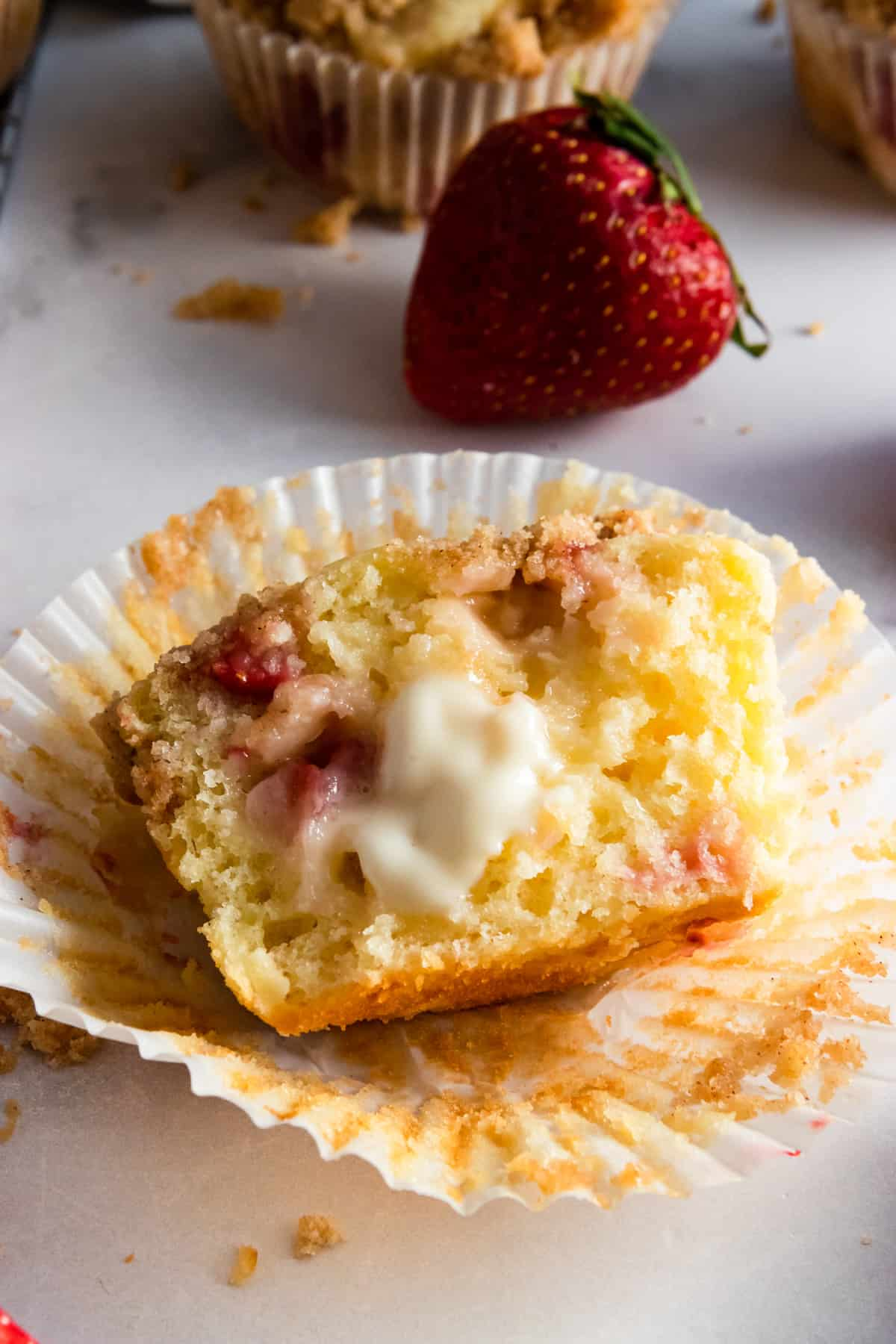 Strawberry muffin cut in half with melted butter on top.