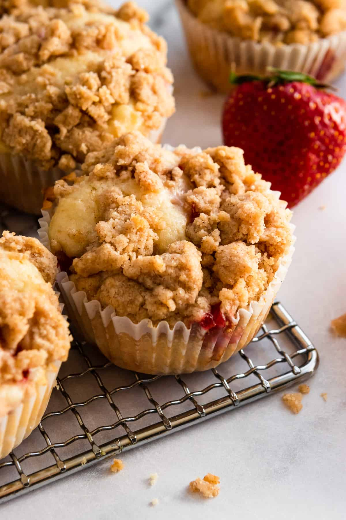 Strawberry muffins on cooling rack with strawberries and crumbs next to it.