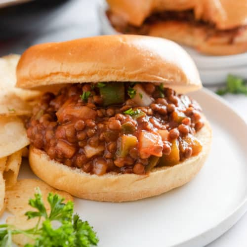Vegan sloppy Joes on bun with chips.